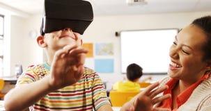 Garçon à l'aide du casque de réalité virtuelle dans la salle de classe banque de vidéos