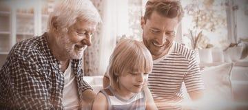 Garçon à l'aide du comprimé numérique avec son père et grand-père dans le salon photographie stock