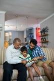 Garçon à l'aide du comprimé tout en se reposant avec le père et le grand-père Photographie stock