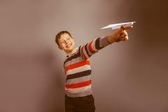 garçon à l'air européen de dix ans jouant le papier Photographie stock libre de droits