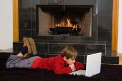 Garçon à la cheminée sur l'ordinateur. Photographie stock libre de droits