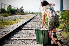Garçon à la gare ferroviaire attendant le train Photographie stock