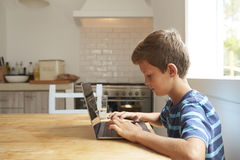 Garçon à la maison utilisant l'ordinateur portable sur la table de cuisine images stock
