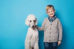 Garçon à la mode avec le chien Amitié pets Portrait de studio au-dessus de fond bleu Images stock