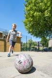 Garçon à un lancement du football de rue photographie stock