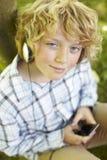 Garçon écoutant le joueur MP3 à l'extérieur image stock