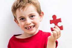 Garçon édenté de sourire trouvant le puzzle spécial pour grandir l'idée image stock