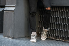 Garçon élégant d'adolescent portant les jeans noirs et les chaussures d'espadrilles se tenant près du mur Images stock