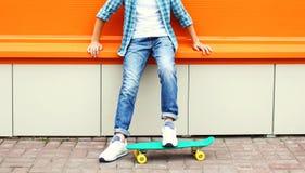 Garçon élégant d'adolescent utilisant une chemise à carreaux et des jeans sur la planche à roulettes Photos stock