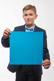 Garçon émotif d'adolescent blond dans un costume bleu avec une feuille de papier bleue pour des notes Image libre de droits