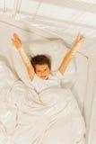 Garçon énergique d'enfant se réveillant dans sa chambre à coucher blanche Photo stock