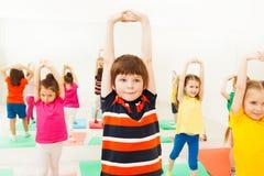 Garçon étirant des mains pendant la leçon de sports dans le gymnase Photographie stock