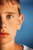 Garçon étonné d'adolescent contre la mer, moitié de visage photo stock