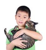 Garçon étreignant avec son chat de tigre mignon d'isolement sur le fond blanc Photographie stock libre de droits