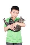 Garçon étreignant avec son chat de tigre mignon d'isolement sur le fond blanc Image stock