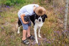 Garçon étreignant le chien de border collie dehors à la ferme Images stock