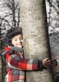 Garçon étreignant un arbre, écoutant les bruits de la nature Image stock