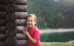 Garçon étreignant une cabane dans un arbre près du lac Image stock