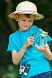 Garçon étudiant le papillon attrapé dans le pot Image libre de droits