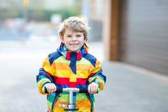 Garçon actif d'enfant d'école dans des vêtements sport colorés montant avec son scooter dans la ville image stock