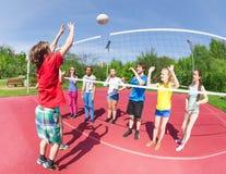 Garçon actif et filles jouant le volleyball ensemble Image stock