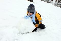 Garçon actif faisant la boule de neige pour le bonhomme de neige photographie stock libre de droits
