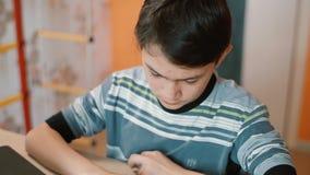 Garçon-adolescent à la table d'ordinateur dactylographiant avec enthousiasme SMS sur le smartphone clips vidéos