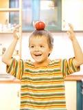 Garçon adorable équilibrant une pomme rouge image stock