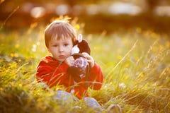Garçon adorable avec son ami de nounours, s'asseyant sur une pelouse Images stock
