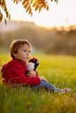 Garçon adorable avec son ami de nounours, s'asseyant sur une pelouse Image stock