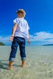 Garçon adorable ayant l'amusement sur la plage tropicale T-shirt blanc, pantalons foncés et lunettes de soleil Nu-pieds sur le sa Images stock