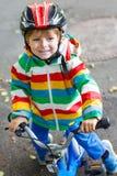 Garçon adorable d'enfant dans le casque rouge et l'imperméable coloré montant le sien Photographie stock libre de droits