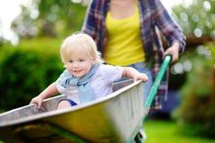 Garçon adorable d'enfant en bas âge ayant l'amusement dans une brouette poussant par la maman dans le jardin domestique, le jour  Photos stock
