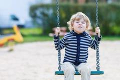 Garçon adorable d'enfant en bas âge ayant l'oscillation de chaîne d'amusement sur le playgroun extérieur Photographie stock libre de droits