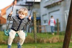 Garçon adorable d'enfant en bas âge ayant l'oscillation de chaîne d'amusement sur le playgroun extérieur Image libre de droits