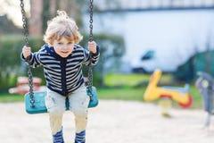 Garçon adorable d'enfant en bas âge ayant l'oscillation de chaîne d'amusement sur le playgroun extérieur Images stock