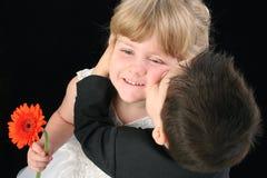 Garçon adorable d'enfant en bas âge embrassant la fille de quatre ans sur la joue Image stock