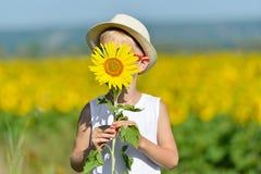 Garçon adorable dans le chapeau se cachant derrière le tournesol sur le champ jaune dehors images stock