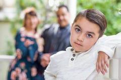 Garçon adorable de métis se tenant devant des parents image stock