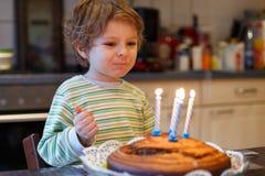 Garçon adorable de quatre ans célébrant son anniversaire et soufflement Photo libre de droits