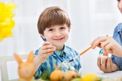 Garçon adorable de sourire d'enfant peignant l'oeuf de pâques Images stock