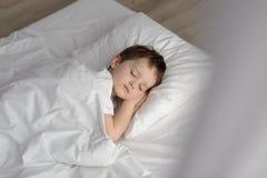 Garçon adorable dormant dans le lit, heure du coucher heureuse dans la chambre à coucher blanche Image libre de droits