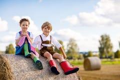 Garçon adorable et fille de petit enfant dans des costumes bavarois traditionnels dans le domaine de blé sur la pile de foin Photos libres de droits