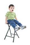 Garçon adorable s'asseyant sur des selles avec l'expression de renversement Photos stock