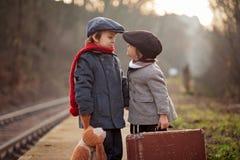 Garçon adorable sur une gare ferroviaire, attendant le train avec l'ours de valise et de nounours image libre de droits
