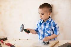 Garçon adorable travaillant avec du bois dans l'atelier Photographie stock libre de droits
