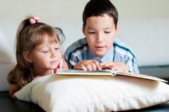 Garçon affichant un livre à sa soeur Images libres de droits