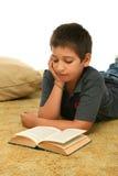 Garçon affichant un livre sur l'étage photos stock