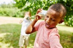 Garçon africain appelle l'ami avec le téléphone de boîte en fer blanc Images stock