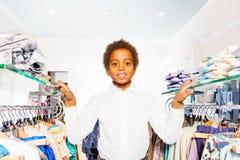 Garçon africain dans le support blanc de chemise entre les cintres Photos libres de droits